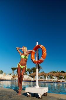 Mulher loira e bonita em pé perto da piscina