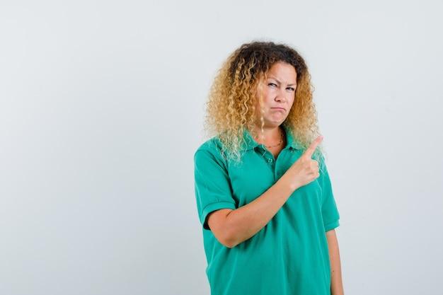 Mulher loira e bonita em uma camiseta pólo verde, apontando para o canto superior direito e parecendo confusa, vista frontal.
