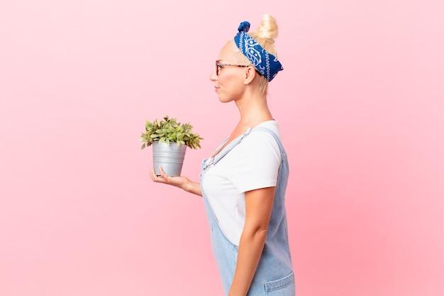 Mulher loira e bonita em vista de perfil pensando, imaginando ou sonhando acordada e segurando uma planta