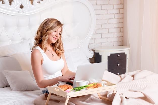 Mulher loira e bonita jovem sentada na cama com o laptop, tomando café da manhã, freelancer ou blogueiro em casa. mulher trabalha no computador de casa.