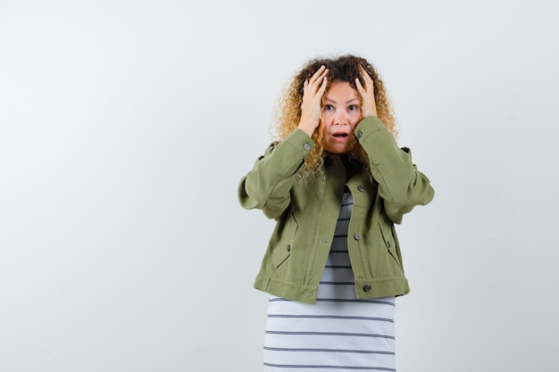 Mulher loira e bonita, mantendo as mãos na cabeça com uma jaqueta verde e parecendo perplexa. vista frontal.
