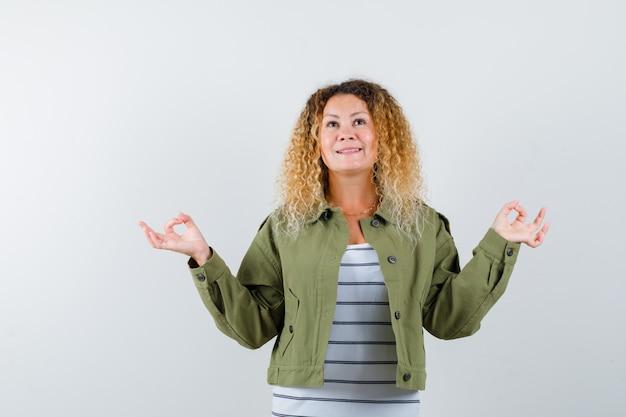 Mulher loira e bonita mostrando gesto de ioga na jaqueta verde e olhando pensativa. vista frontal.