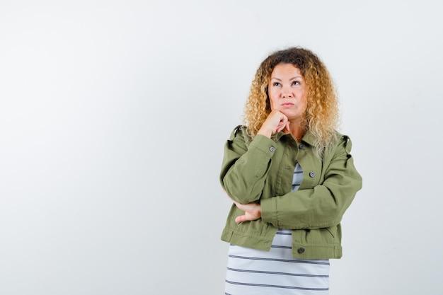 Mulher loira e bonita na jaqueta verde, apoiando o queixo na mão e olhando pensativa, vista frontal.
