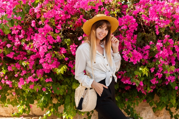 Mulher loira e bonita no chapéu de palha posando sobre rosa árvore florescendo em dia ensolarado de primavera