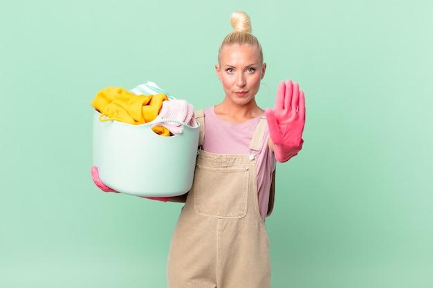 Mulher loira e bonita olhando séria, mostrando a palma da mão aberta fazendo gesto de parar de lavar roupa conceito