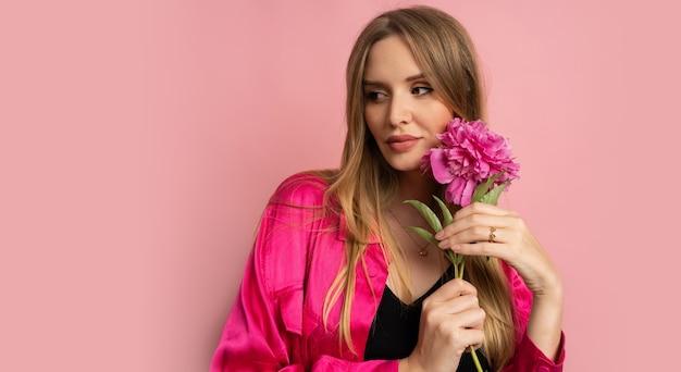Mulher loira e bonita posando com uma flor de peônia em uma roupa elegante de verão sobre uma parede rosa