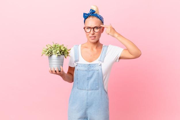 Mulher loira e bonita se sentindo confusa e intrigada, mostrando que você é louco e segurando uma planta