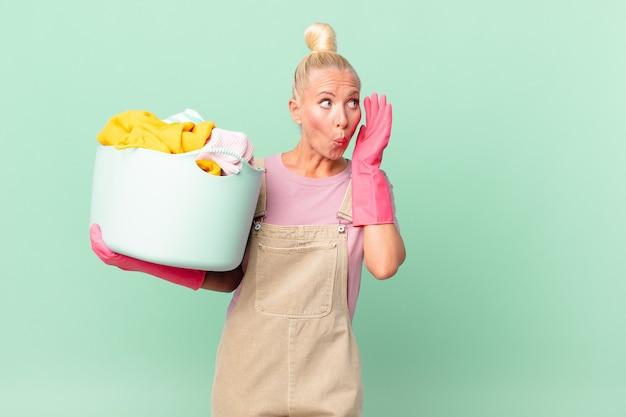 Mulher loira e bonita se sentindo feliz, animada e surpresa lavando roupas conceito