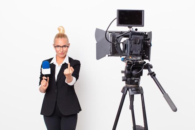 Mulher loira e bonita se sentindo irritada, irritada, rebelde e agressiva e segurando um microfone. conceito de apresentador