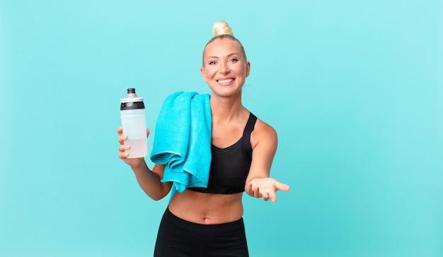 Mulher loira e bonita sorrindo alegremente com simpáticos e oferecendo e mostrando um conceito. conceito de fitness