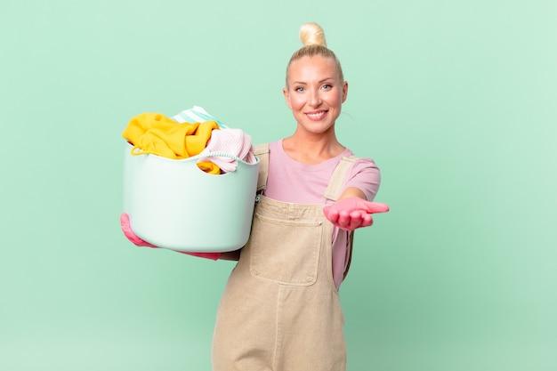 Mulher loira e bonita sorrindo feliz com simpatia e oferecendo e mostrando um conceito de lavagem de roupas