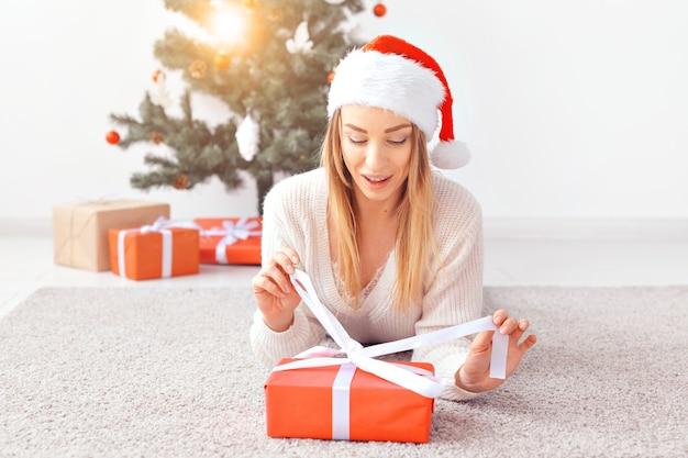 Mulher loira e bonita, vestindo um suéter de malha quente, deitada sobre um tapete perto da árvore de natal decorada em uma sala de estar. muitos presentes debaixo da árvore.
