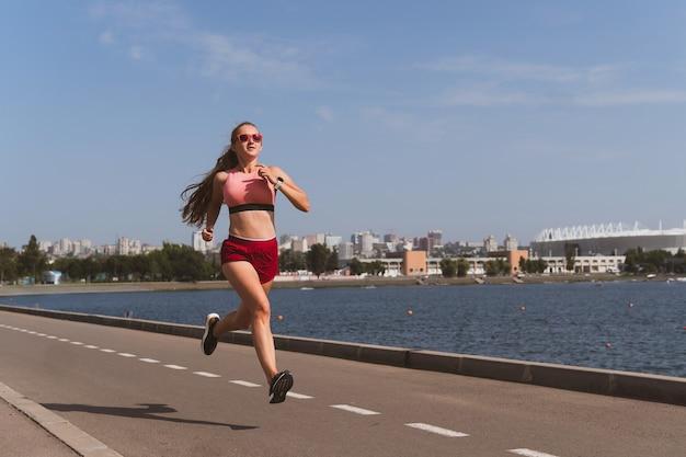 Mulher loira e esportiva com cabelo comprido correndo no estádio