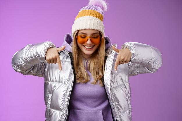 Mulher loira elegante alegre em óculos de sol elegantes de jaqueta prateada jat apreciando montanhas perfeitas vista resort de férias nevado olhar apontando para baixo sorrindo divertido se divertindo sentir feliz, fundo roxo.