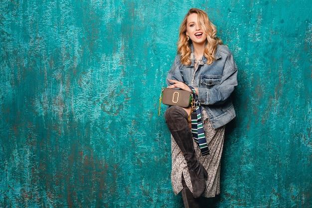 Mulher loira elegante atraente e sexy em jeans e jaqueta grande caminhando contra uma parede verde vintage na rua