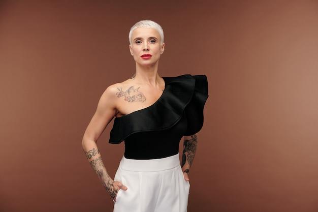 Mulher loira elegante com camiseta preta e calça branca com tatuagens nos braços, pescoço e peito, em pé na frente da câmera, isolada
