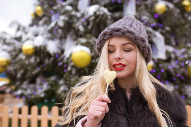 Mulher loira elegante com chapéu de tricô cinza segurando bombons de chocolate contra o abeto de natal