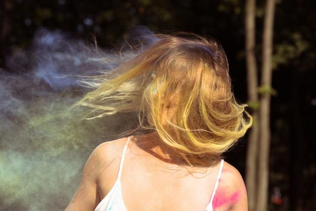Mulher loira elegante com o vento no cabelo posando no festival holi
