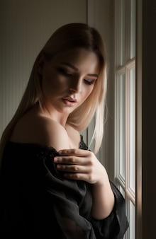 Mulher loira elegante com ombros nus posando em um quarto escuro