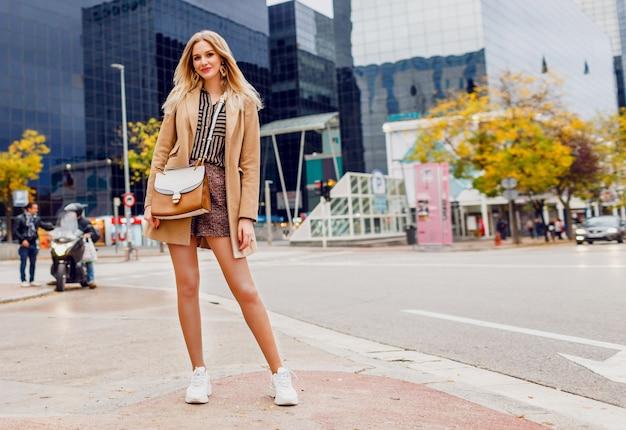 Mulher loira elegante com roupa casual de primavera, caminhando ao ar livre e curtindo as férias na grande cidade moderna. vestindo casaco de lã bege e blusa listrada. comprimento total.