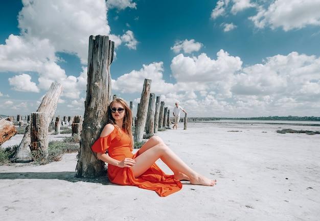 Mulher loira elegante com vestido vermelho na praia