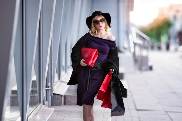 Mulher loira elegante de casaco preto, óculos escuros e chapéu com sacolas de compras, passeando pela rua, show de feriado Foto Premium