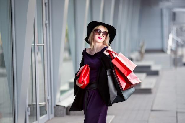 Mulher loira elegante de casaco preto, óculos escuros e chapéu com sacolas de compras, passeando pela rua, show de feriado