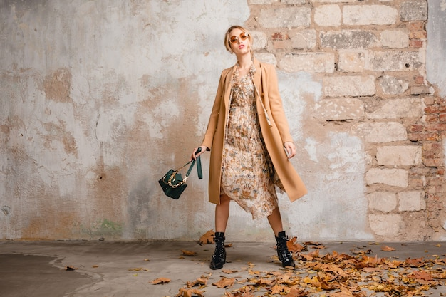 Mulher loira elegante e atraente com casaco bege caminhando na rua contra uma parede vintage