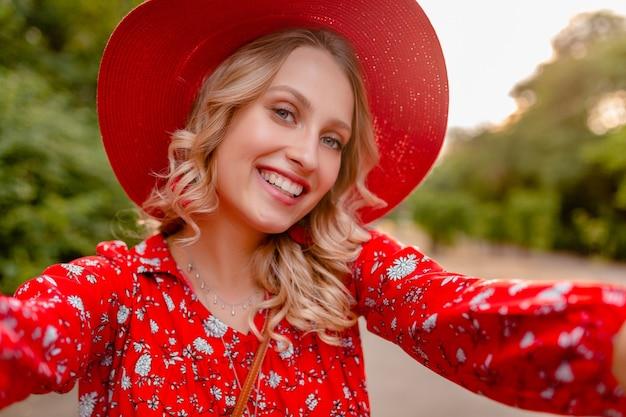 Mulher loira elegante e atraente e sorridente com chapéu vermelho palha e blusa, roupa da moda de verão, tirando foto de selfie na câmera do telefone