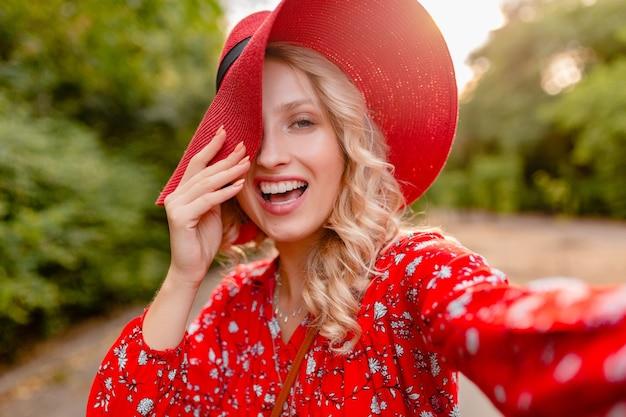 Mulher loira elegante e atraente e sorridente com chapéu vermelho palha e blusa, roupa da moda de verão, tirando foto de selfie