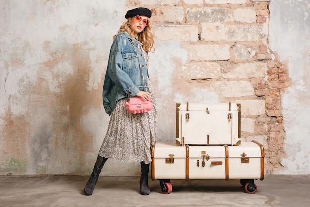 Mulher loira elegante e atraente em jeans e jaqueta grande andando contra a parede na rua