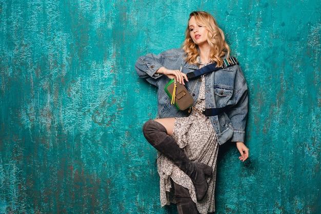 Mulher loira elegante e atraente em jeans e jaqueta grande caminhando contra uma parede verde vintage na rua