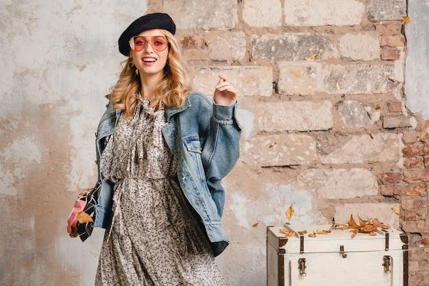 Mulher loira elegante e atraente em jeans e jaqueta grande posando contra a parede na rua