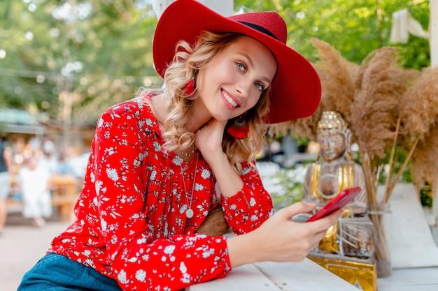 Mulher loira elegante e atraente sorridente com chapéu vermelho palha e blusa, roupa da moda de verão segurando usando smart phone cafe