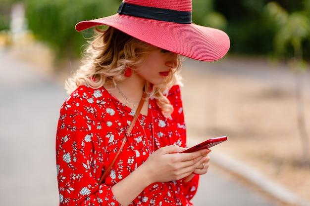 Mulher loira elegante e atraente sorridente com chapéu vermelho palha e blusa roupa da moda de verão usando telefone