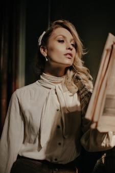 Mulher loira elegante e autoconfiante usando blusa branca e calça marrom, lendo jornal e fazendo poses em um corredor escuro