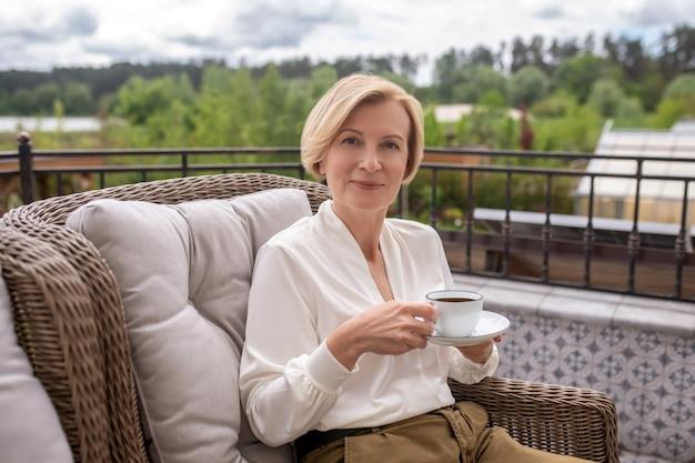 Mulher loira elegante e calma tomando café ao ar livre
