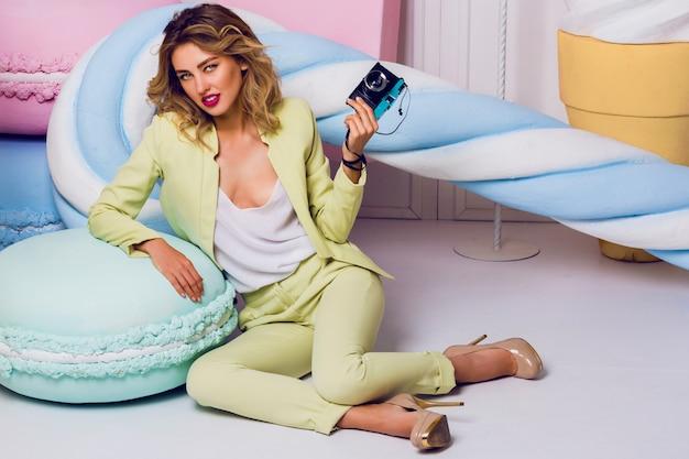 Mulher loira elegante elegante posando no estúdio com doces em terno pastel casual. fundo de objetos doces e confeitos. cores pastel suaves.