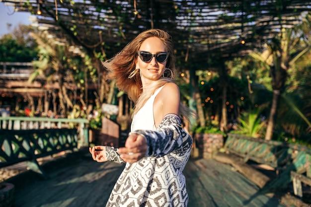 Mulher loira elegante em trajes de banho brancos em lugar exótico
