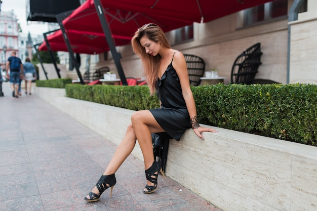 Mulher loira elegante em um vestido preto casual elegante, sentada perto de restaurante de luxo. modelo encantador descansando no centro da cidade.