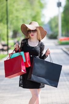 Mulher loira elegante em um vestido preto, óculos escuros e chapéu com sacolas de compras andando pela cidade