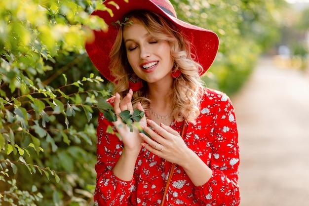 Mulher loira elegante muito atraente e sorridente com chapéu vermelho palha e blusa roupa da moda de verão