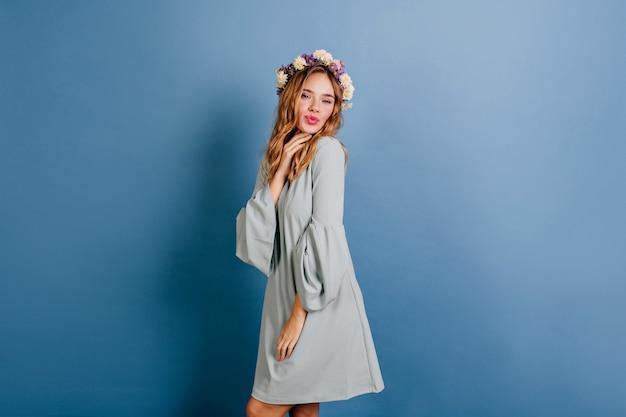 Mulher loira elegante posando com expressão facial de beijo na parede azul
