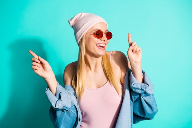 Mulher loira elegante posando contra a parede azul