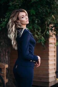 Mulher loira elegante terno azul escuro com botões de ouro