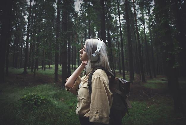 Mulher loira em fones de ouvido com mochila em dia chuvoso na floresta