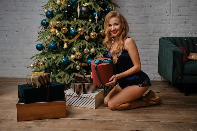 Mulher loira em lingerie azul sexy está sorrindo, posando sentada perto da árvore de natal decorada e segurando uma caixa de presente. celebração de ano novo. fechar-se.