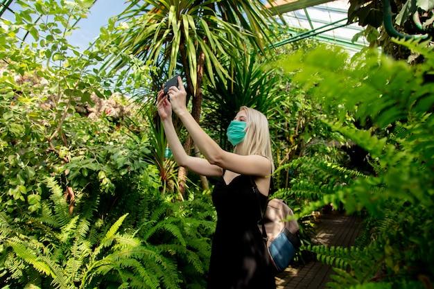 Mulher loira em máscara facial com telefone celular em estufa de palma do jardim botânico