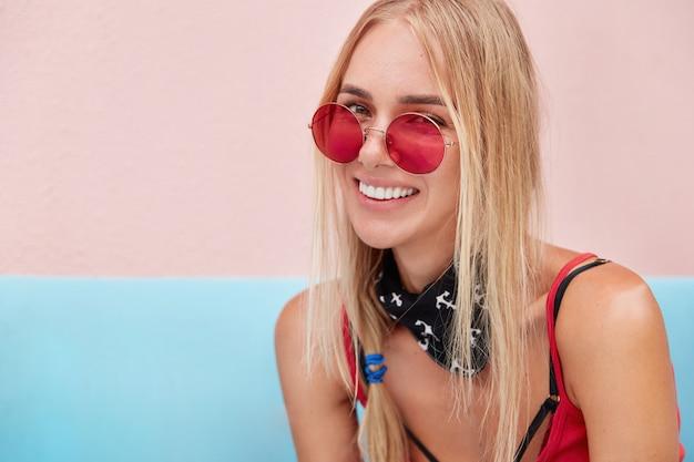 Mulher loira em óculos de sol da moda, usa roupas da moda e óculos de sol vermelhos, senta-se contra a parede rosa em um sofá confortável.