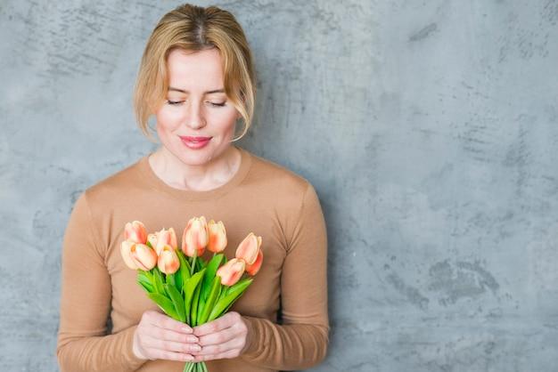 Mulher loira em pé com buquê de tulipas